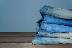 Blue jean and jean lack texture on the wooden floor. Pattern of blue jeans are overlapping on the table Royalty Free Stock Photos