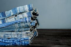 Blue jean and jean lack texture on the wooden floor. Pattern of blue jeans are overlapping on the table Stock Photos