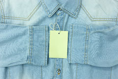 Blue jean shirt with empty tag for background. Blue jean shirt with empty tag for background Stock Photography