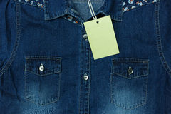 Blue jean shirt with empty tag for background. Blue jean shirt with empty tag for background Royalty Free Stock Photo