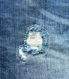 Blue jean texture with a hole and threads showing Royalty Free Stock Photo