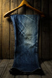 Blue jean with wood hanger on wood background, low key image Stock Photography
