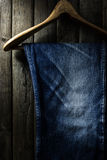 Blue jean with wood hanger on wood background, low key image Royalty Free Stock Image