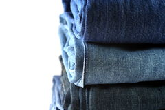 Blue jeans. Folded and stacked blue jeans on a white background Royalty Free Stock Photography