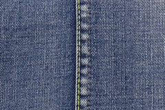 Blue jeans background with yellow seam. Royalty Free Stock Images