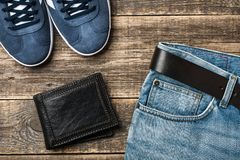 Blue Jeans with belt, shoes and leather wallet on wooden background stock image