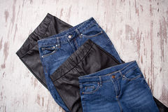 Blue jeans and black leather leggings, assortment. Fashionable concept. View from above Royalty Free Stock Photos