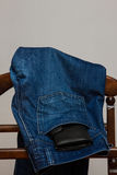 Blue jeans with a black purse hanging on a wooden hanger Royalty Free Stock Images