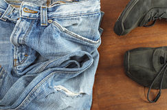 Blue jeans with black shoes on wooden background Royalty Free Stock Photography