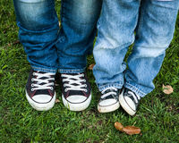 Blue jeans and black and white shoes adult and child Stock Photography