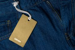 Blue jeans with blank brown label tag. Blank brown paper mockup Stock Photos