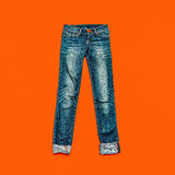 Blue jeans. On bright orange background Stock Images