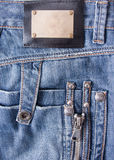 Blue jeans with bronze label Stock Photos