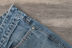 Blue jeans on a brown wooden background stock image