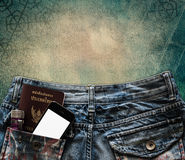 Blue jeans with cell phone, flashlight and passport in a pocket Stock Image