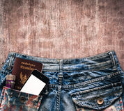 Blue jeans with cell phone, flashlight and passport in a pocket Stock Photo