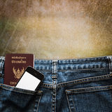 Blue jeans with cell phone and passport in a pocket background Royalty Free Stock Photography