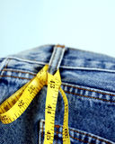 Blue jeans denim and yellow measure tape Royalty Free Stock Photo