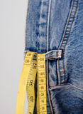Blue jeans denim and yellow measure tape Royalty Free Stock Photography