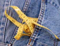 Blue jeans denim and yellow measure tape Royalty Free Stock Images