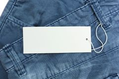 Blue jeans detail with white blank tag, close up royalty free stock image