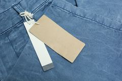 Blue jeans detail with white and brown blank tags, close up stock image