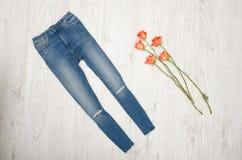 Blue jeans e rose arancio su un fondo di legno Concetto alla moda, vista superiore Fotografie Stock