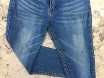 Blue Jeans falteten ein Bein auf Zementboden lizenzfreie stockbilder