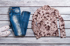 Blue jeans and floral pullover. Sweatshirt with flower print. Girl's outfit with stylish top. Trendy spring look Royalty Free Stock Photography