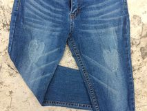 Blue jeans folded one leg on cement floor. royalty free stock images