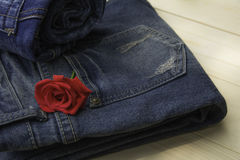 Blue jeans folded with red rose on wooden table and on wooden ba Stock Images