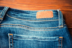 Blue jeans with half of back pocket and brown leather tag. On wood table background. Shallow depth of field Stock Photos