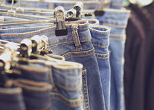 Blue jeans on hanger, store background Royalty Free Stock Photo