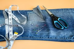 Blue jeans with a large hole on a pant leg below the knee, multi coloured headed sewing pins, tailor tape and scissors. Blue jeans with a large hole on a pant stock images
