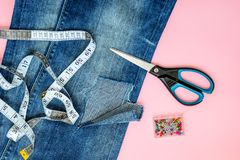 Blue jeans with large hole on a pant leg below the knee, sewing pins, tailor tape and scissors. Blue jeans with large hole on a pant leg below the knee, multi stock photography