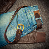 Blue jeans, a leather belt with a buckle and leather jacket Royalty Free Stock Image
