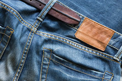 Blue jeans with leather belt and tag Royalty Free Stock Photography
