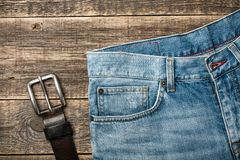 Blue Jeans and leather belt on wooden background Royalty Free Stock Photo
