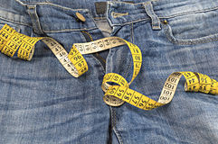 Blue jeans with measuring tape. Royalty Free Stock Images