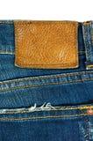 Blue Jeans mit ledernem Aufkleber auf Weiß Lizenzfreie Stockfotografie