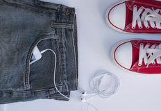 Blue jeans with mobile phone in the pocket near Youth red shoes royalty free stock photography