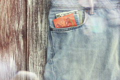 Blue jeans with money in the pocket. On the background of vintage boards. Lens flare effect Royalty Free Stock Photos