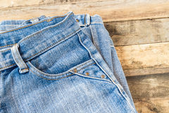 Blue jeans on old wooden surface Royalty Free Stock Photography