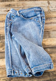 Blue jeans on old wooden surface Royalty Free Stock Photos