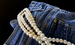 Blue Jeans and Pearls. Opposites attract in fashion. Denim blue jeans and pearls jewelry together. Isolated against a black backdrop Royalty Free Stock Image