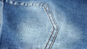 Blue jeans pocket on brown cloth, cam moves to the stock footage