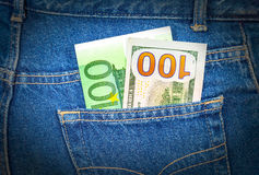 Blue jeans pocket with one hundred euro and one hundred american Royalty Free Stock Images