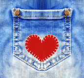 Blue jeans with pocket and red heart. Closeup royalty free stock photos