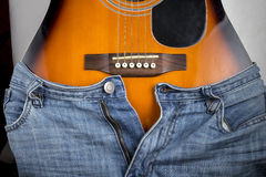 Blue jeans put on an acoustic guitar, which is similar to the cu Royalty Free Stock Image