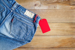 Blue jeans with red blank tag on wooden background Royalty Free Stock Photo